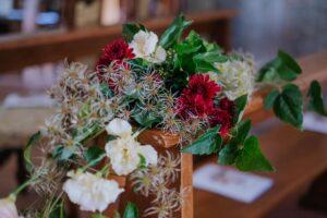 Decorazioni panche chiesa con edera, rose rosse | organizzatrice eventi Siena Toscana