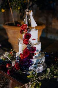 Torta di nozze a 3 piani con fiori rosse e tocchi blu | wedding planner Siena Toscana